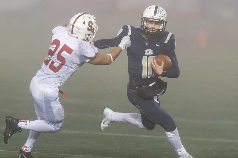 STAFF PHOTO: CHRISTOPHER OERTELL - Banks' Hayden Vandehey stiff arms a Seaside tackler during the Braves' game against Seaside, Nov. 24, at Hillsboro Stadium.