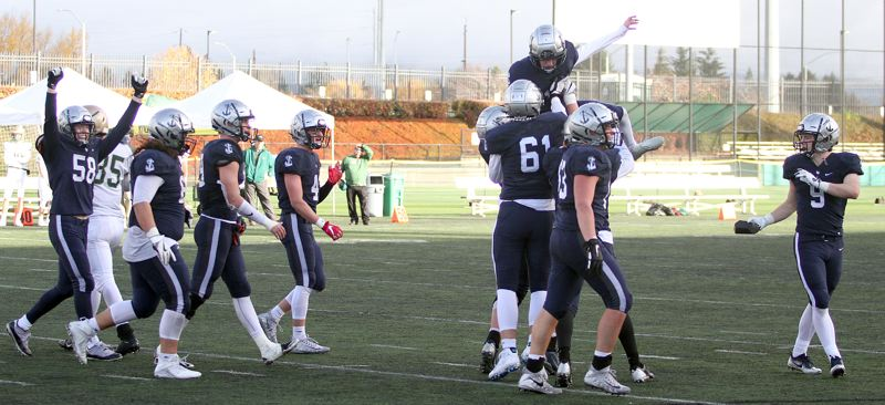 REVIEW PHOTO: MILES VANCE - Lake Oswego kicker Diyar Dezay (center-right) gets lifted into the air after his 31-yard field provided the final points in his team's 24-14 win over Jesuit in the Class 6A state semifinals on Friday at Hillsboro Stadium.