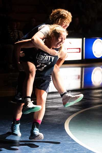 STAFF PHOTO: CHRISTOPHER OERTELL - Liberty's Livia Knapp rides the back of teammate Maliah Jobe as part of a relay race during the Liberty Late Night event Tuesday, Nov. 20, at Liberty High School.