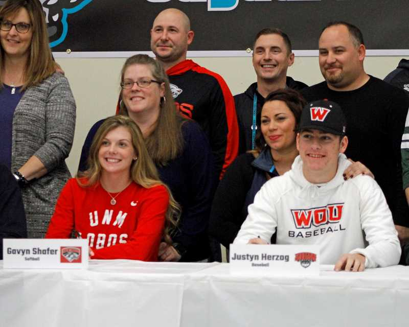STAFF PHOTO: WADE EVANSON - Century's Gavyn Shafer (left) and Justyn Herzog (right) sign their letters of intent in front of family and friends at a ceremony at Century High School.