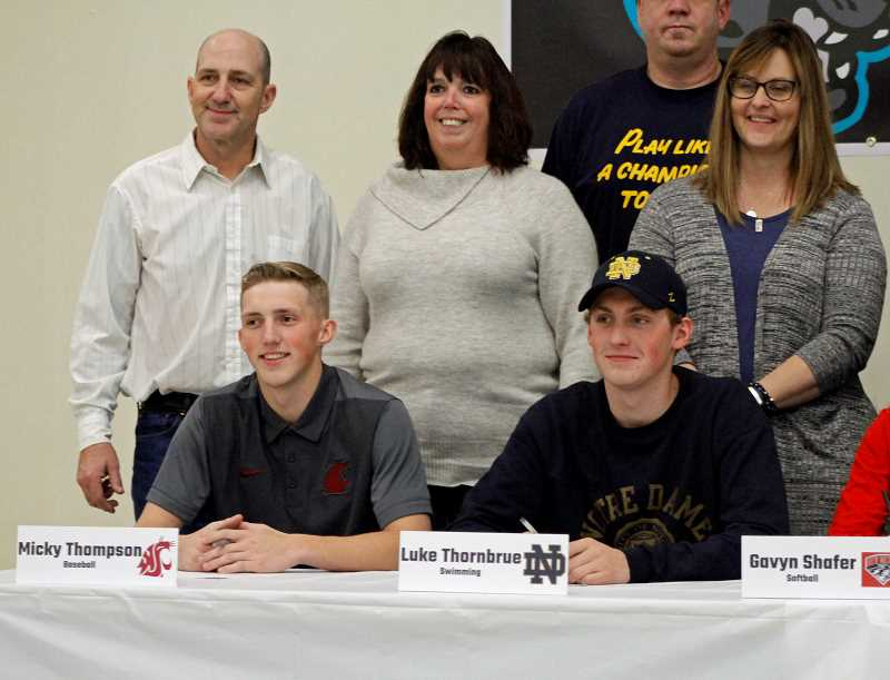 STAFF PHOTO: WADE EVANSON - Century's Micky Thompson (left) and Luke Thornbrue (right) sign their letters of intent in front of family and friends at a ceremony at Century High School.