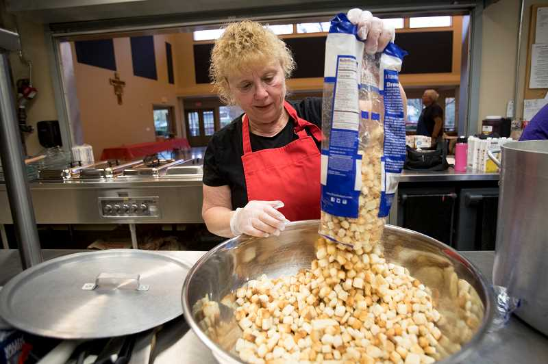 SPOKESMAN PHOTO: JAIME VALDEZ - Joanie Kruse, a parishioner of St Cyrils Catholic Church, prepares the ingredients for stuffing in preparation for a Thanksgiving meal at the church in Wilsonville. The church has been providing a meal for those who dont have anybody to share for the holiday the last five years.