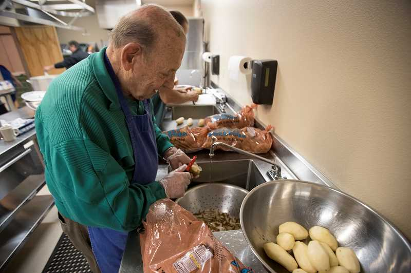 SPOKESMAN PHOTO: JAIME VALDEZ - Leo Bottaini, a parishioner of St Cyrils Catholic Church, peels potatoes for mashed potatoes in preparation for a Thanksgiving meal at the church in Wilsonville. The church has been providing a meal for those who dont have anybody to share for the holiday the last five years.