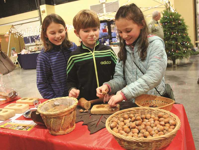 INDEPENDENT FILE PHOTO - Salem residents and siblings, from left, Lillian, Henry and Rose Langen Swartzendruber take turns cracking hazelnuts with a wooden mallet at the Hazelnut Fest a few years ago.