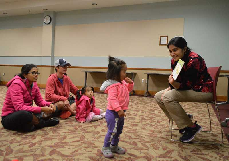 STAFF PHOTO: JANAE EASLON - Bakul Godbole, a library assistant at Hillsboro Brookwood Library, reads 'Watch Out' to international storytime families.