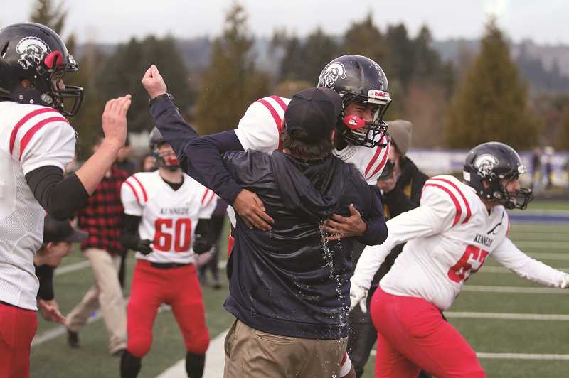 PHIL HAWKINS - Kennedy senior Brandon Salazar leaps into the arms of head coach Joe Panuke as the final seconds count down in the Trojans' 31-20 victory over the Santiam Wolverines in the 2018 2A Football State Championship.