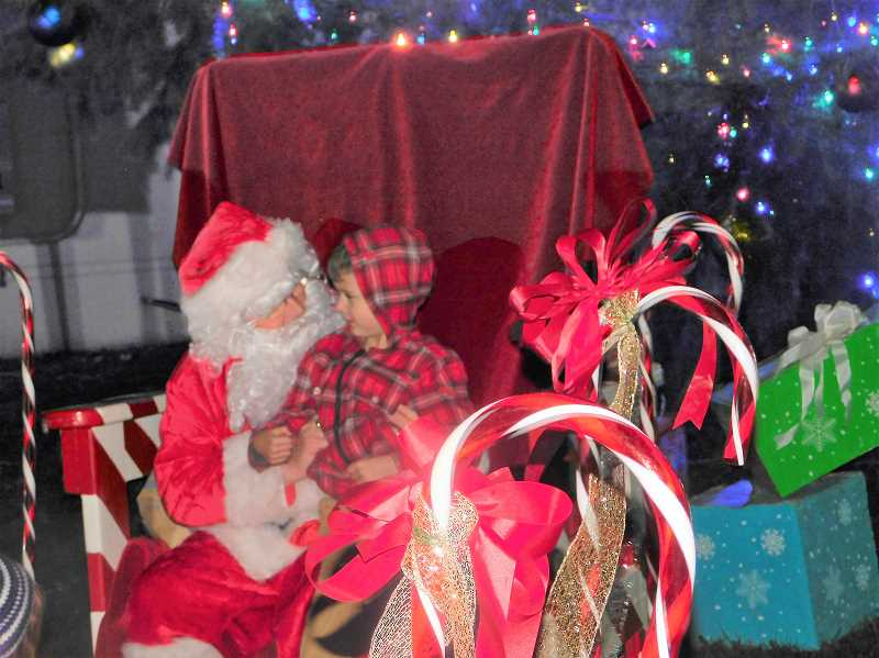 FILE PHOTO - Santa Claus visits with a young Estacada resident during last years tree lighting. He will also appear at this years event, which is scheduled for Friday, Nov. 30.