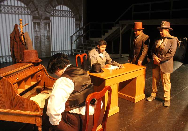 SUSAN MATHENY/MADRAS PIONEER - Bob Cratchit (played by Julia Horn), left, works at his desk as two solicitors unsuccessfully ask Scrooge, center at the desk, for donations for the poor.