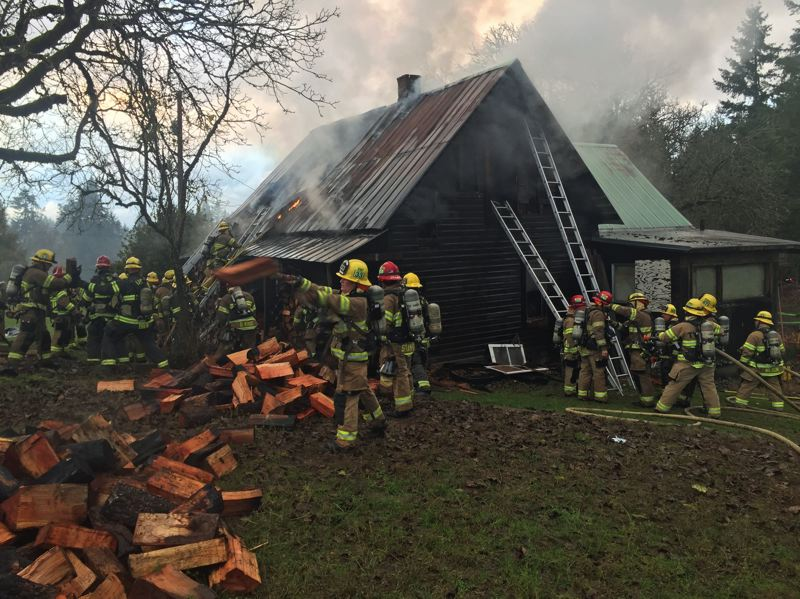 PHOTO: TVF&R - Crews move stacks of firewood away from a rural house while battling a second-story fire on Wednesday, Nov. 28.