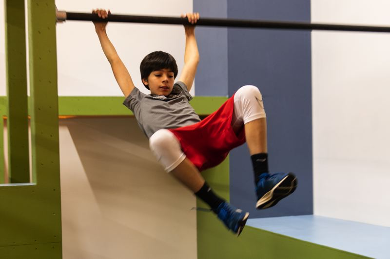 STAFF PHOTO: CHRISTOPHER OERTELL - Micah Elmers swings on a pipe at Hillsboro's new parkour gym where participants learn how to efficiently get from point A to point B.