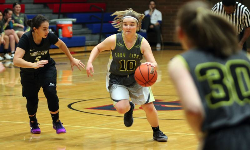 PAMPLIN MEDIA GROUP PHOTO: JIM BESEDA - St. Helens point guard Emelia Paullus moves the ball up the court under pressure from Ridgeviews Marley Sargent during Wednesday's jamboree hosted by La Salle Prep.