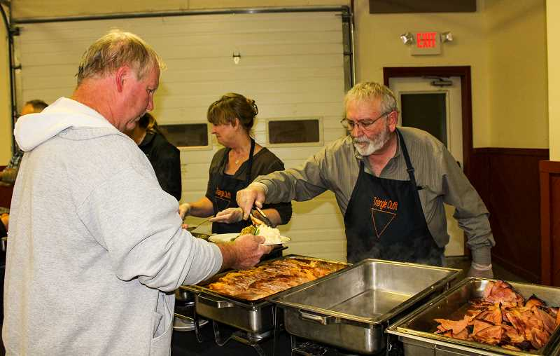 HOLLY SCHOLZ/CENTRAL OREGONIAN   - Crook County Commissioner Brian Barney, right, serves turkey to Greg Gissel. Gissel served in the U.S. Army from 1974 to 1977 in Texas and Germany.