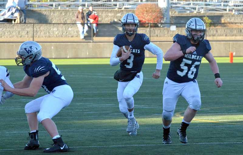 SPOKESMAN PHOTO: TANNER RUSS - Quarterback Nathan Overholt follows behind senior lineman Caleb Baker on a run play.