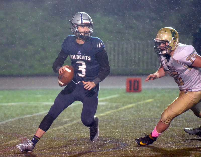 SPOKESMAN PHOTO: TANNER RUSS - Senior quarterback Nathan Overholt scrambles to evade a Pendletondefender in the league championship game. Wilsonville starched thevisiting Buckeroos 53-7.