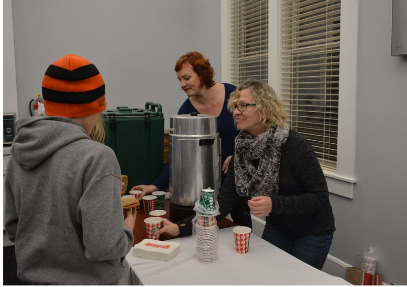 SPOTLIGHT PHOTO: COURTNEY VAUGHN - Scappoose Community Club volunteers Amy McMullen and Sandra Brown Loos serve hot chocolate to visitors at the Scappoose Public Library during a Heritage Park lighting event Monday, Nov. 26.