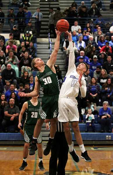 PHIL HAWKINS - North Marion's Nic Iliyn (left) and Woodburn's Tyson Doman leap for the opening tipoff in Friday night's season opener. Woodburn went on to win 82-63.
