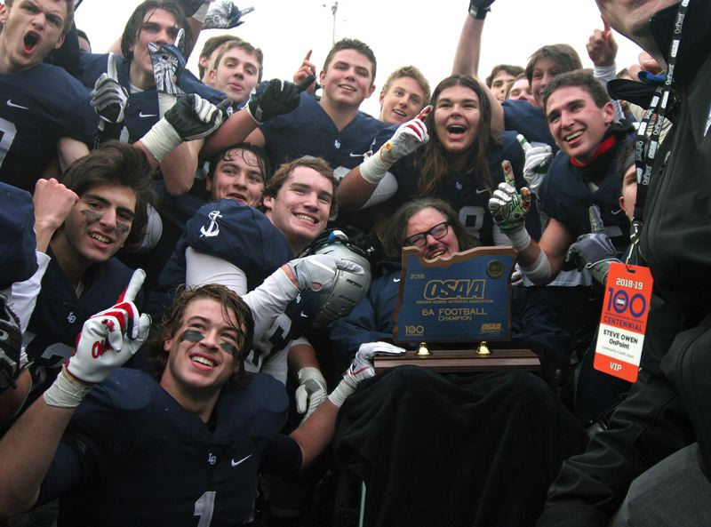 REVIEW PHOTO: MILES VANCE - Lake Oswego players crowd around Laker assistant coach Jeff Young (behind trophy) to celebrate their 34-27 win over Sheldon in the Class 6A state football championship at Hillsboro Stadium on Saturday.