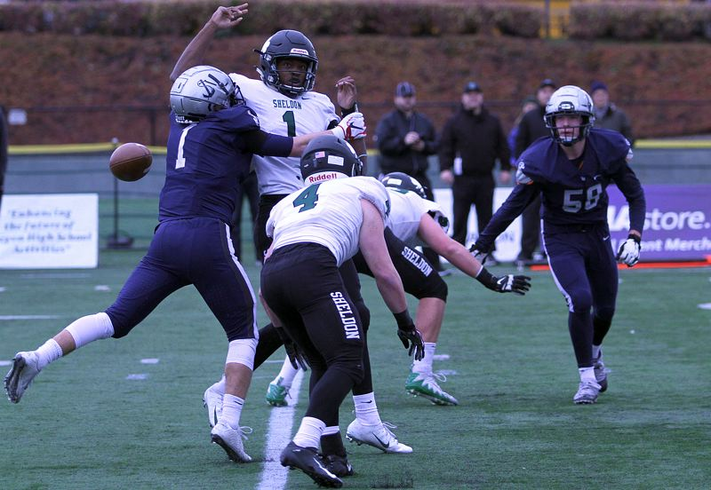 REVIEW PHOTO: MILES VANCE - Lake Oswego senior Keenan DeRaeve forces Sheldon's Michael Johnson Jr. to fumble during the Lakers' 34-27 state championship win on Saturday at Hillsboro Stadium.