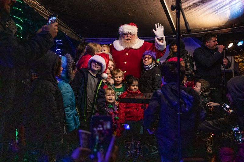 TIMES PHOTO: JONATHAN HOUSE - Children rush to have their photos taken with Santa Claus Friday night, Nov. 30, during the Christmas tree-lighting at Beaverton City Park.