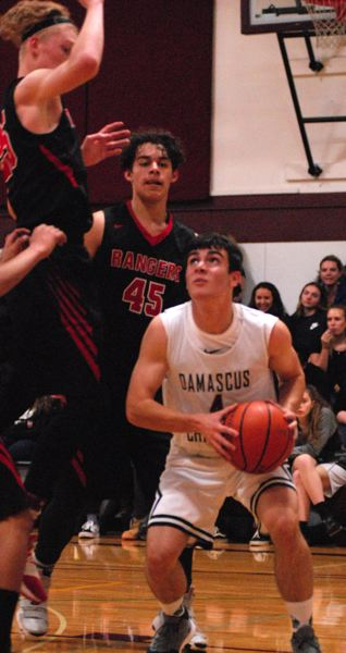 OUTLOOK PHOTO: DAVID BALL - Damascus Christians Luke Nelson waits for traffic to clear under the basket.