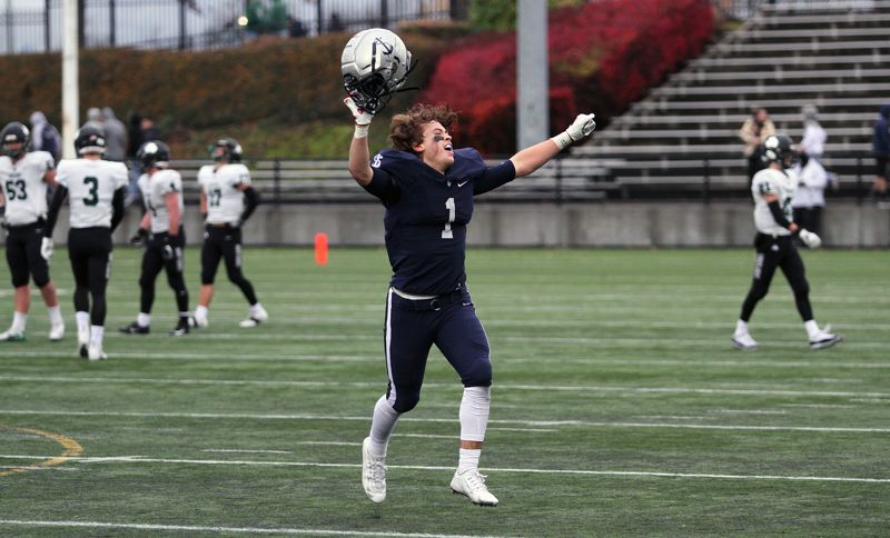 REVIEW PHOTO: MILES VANCE - Lake Oswego senior running back/linebacker Keenan DeRaeve leaps for joy after his Lakers beat Sheldon 34-27 to win the Class 6A state championship at Hillsboro Stadium on Saturday.
