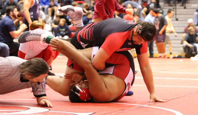 PAMPLIN MEDIA: JIM BESEDA - Oregon City heavyweight Lane Marshall rolls North Medford's Devin Crenshaw onto his back for a first-round pin in the semifinals of Saturday's 21-team Tyrone S. Woods Memorial Tournament.