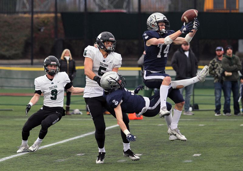 REVIEW PHOTO: MILES VANCE - Lake Oswego's Thomas Dukart (right) and Joe Hutson break up a fourth-quarter pass intended for Sheldon's Patrick Herbert (No. 5) in Saturday's Class 6A state championship game at Hillsboro Stadium.