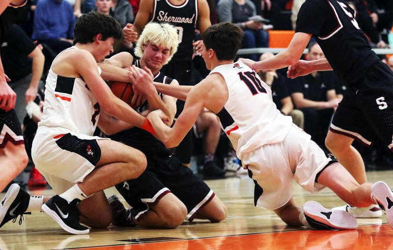 TIMES PHOTO: DAN BROOD - Sherwood junior Blake Jensen (center) battles Beaverton's Bennett Giebles (left) and Cody Davidson for the ball during Friday's season-opener.