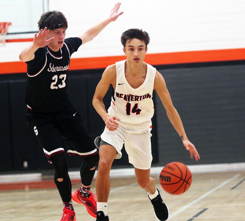 TIMES PHOTO: DAN BROOD - Sherwood senior Charlie Bulfinch (left) puts the pressure on Beaverton senior Mason Stewart-Carothers during Friday's game.