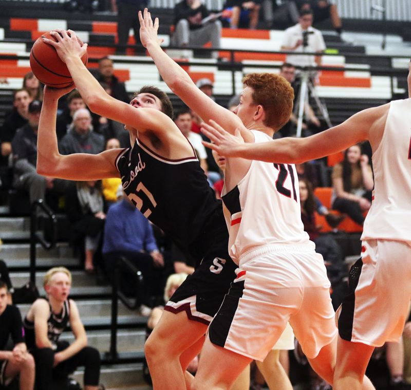 TIMES PHOTO: DAN BROOD - Sherwood senior Braden Thorn (left) looks to go up to the basket against Beaverton senior John Oleson during Friday's game.