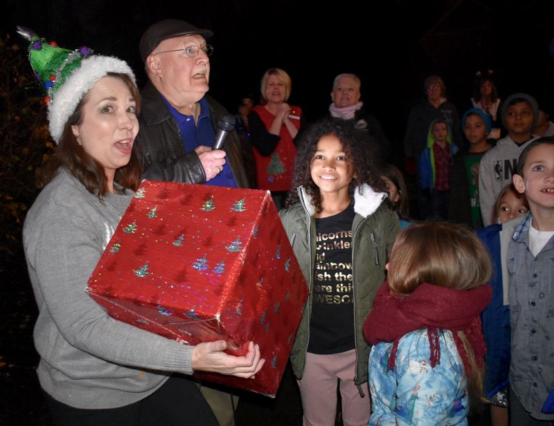 OUTLOOK PHOTO: MATT DEBOW - Jazmine DiSalvo reacts to pushing the button that lights up Fairviews Christmas tree on Saturday, Dec. 1. Ginell Cooper and Fairview City Councilor Mike Weatherby react to seeing the lights for the first time.