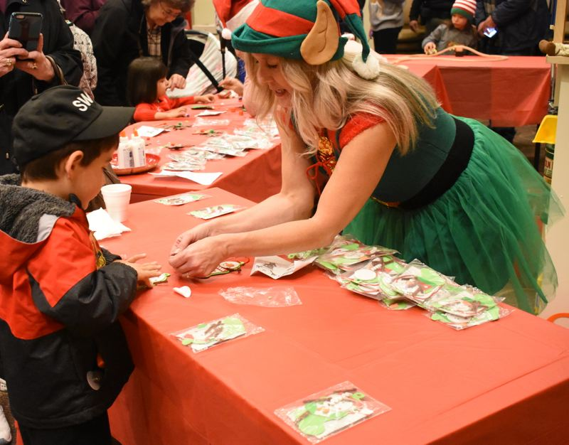 OUTLOOK PHOTO: MATT DEBOW - Denise McGinn helps 3-year-old Jacob DeYoung put together an ornament at Fairview City Hall during the citys annual Christmas festivities.