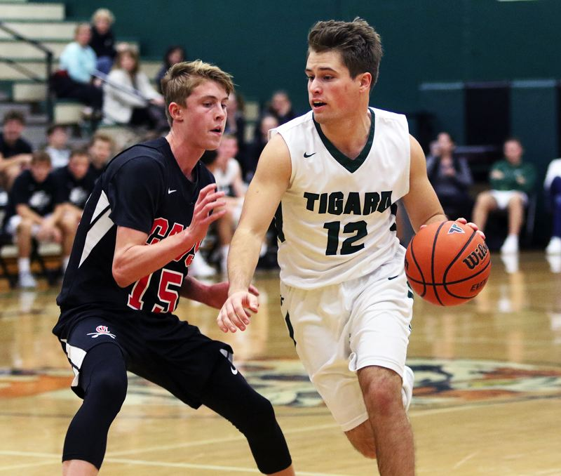TIMES PHOTO: DAN BROOD - Tigard senior Carson Crist (right) looks to drive against Clackamas sophomore Jack Dorn during Saturday's game.