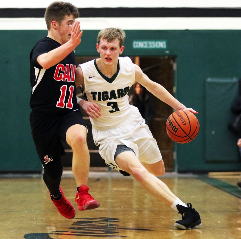 TIMES PHOTO: DAN BROOD - Tigard senior Jake Bullard (right) brings the ball up court against Clackamas junior Artur Gavrilovich.