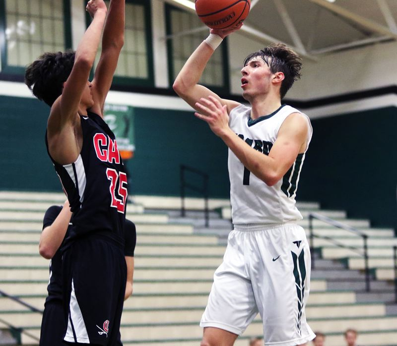 TIMES PHOTO: DAN BROOD - Tigard senior Diego Lopez (right) looks to shoot over Clackamas senior David Aspidov during Saturday's game.