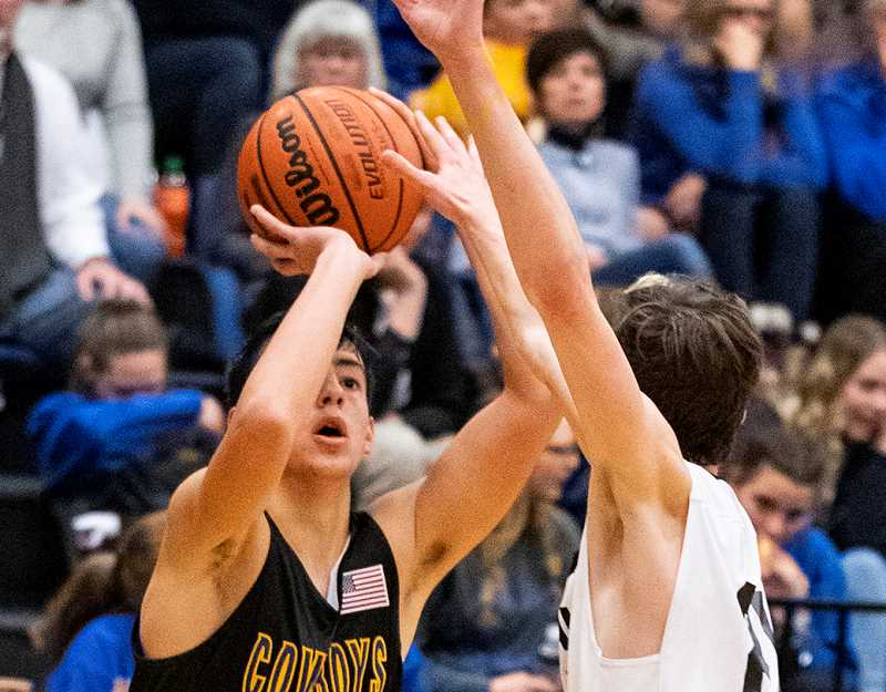 LON AUSTIN/CENTRAL OREGONIAN - Jordan Graydon goes up for a basket during the Cowboys' win over the Sisters Outlaws last Friday. Crook County has three road games this week, before playing their first home game on Tuesday, Dec. 11, when they host La Pine.