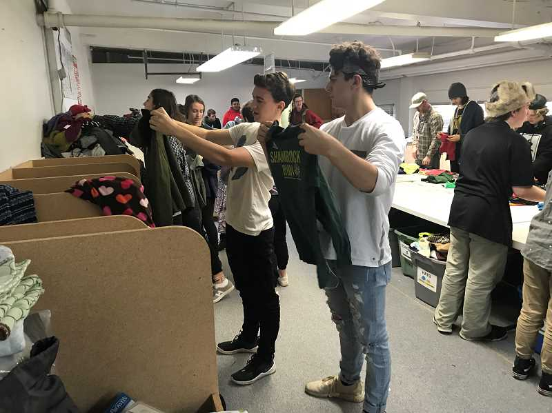 SUBMITTED PHOTO  - Art Tech students help sort and organize children's clothes.