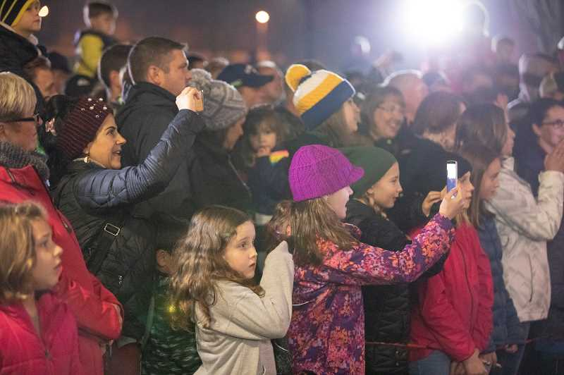SPOKESMAN PHOTO: JONATHAN HOUSE - Friends and family of the Boeckman Creek Primary Junior Choir film during their performance at the Wilsonville Christmas Tree Lighting.