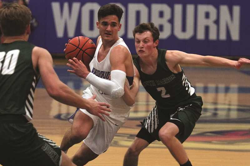 PHIL HAWKINS - Woodburn senior R.J. Veliz drives to the hole against North Marion's Brady Hansen, as Nic Iliyn waits in the paint to defend. Veliz finished the game with 34 points in his debut with the Bulldogs after transferring from Blanchet Catholic prior to the school year.
