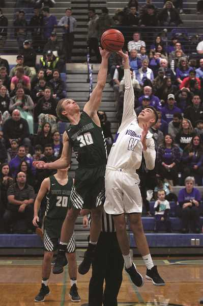 PHIL HAWKINS - North Marion's Nic liyn and Woodburn's Tyson Doman square off for the opening tip in front of a packed crowd at Woodburn High School on Friday evening.