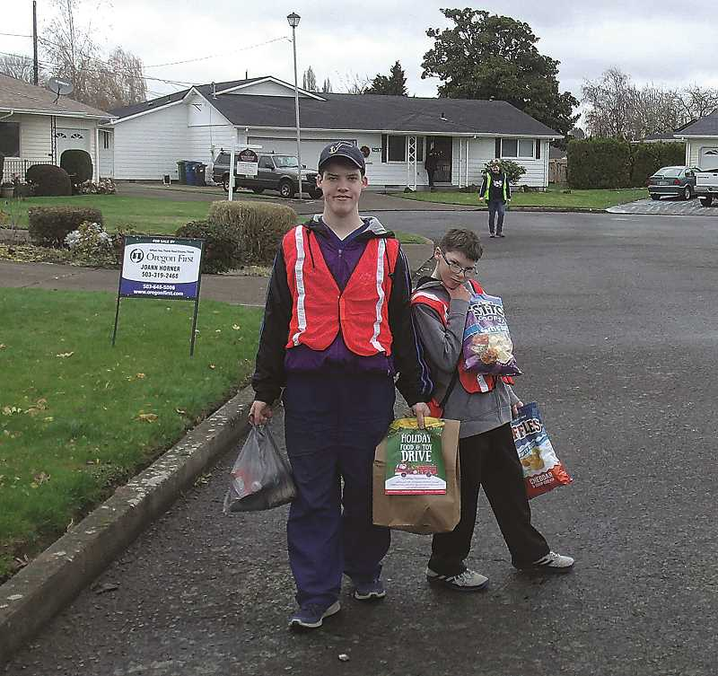 JUSTIN MUCH - A couple of local scouts collect food in the Woodburn Estates & Golf neighborhood during the 29th Annual Food Drive Saturday, Dec. 1.