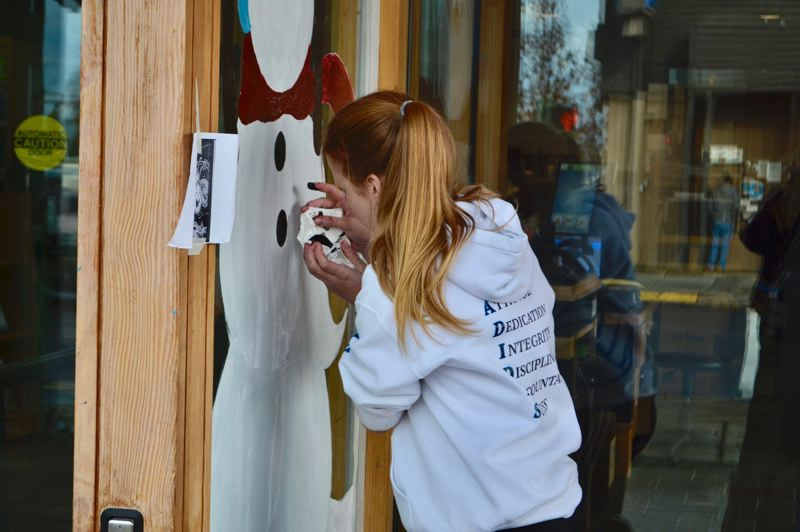 POST PHOTO: BRITTANY ALLEN - Students from all grades at Sandy High School participated in painting Sandy businesses' windows with holiday cheer on Nov. 30.