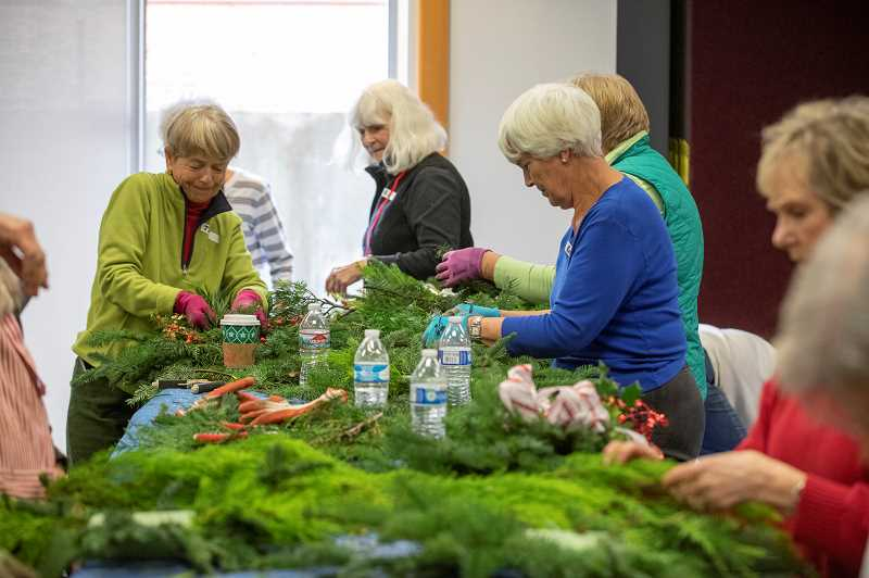 SPOKESMAN PHOTO: JONATHAN HOUSE - Members of the Wilsonville Garden Club make wreaths for the upcoming benefit sale.