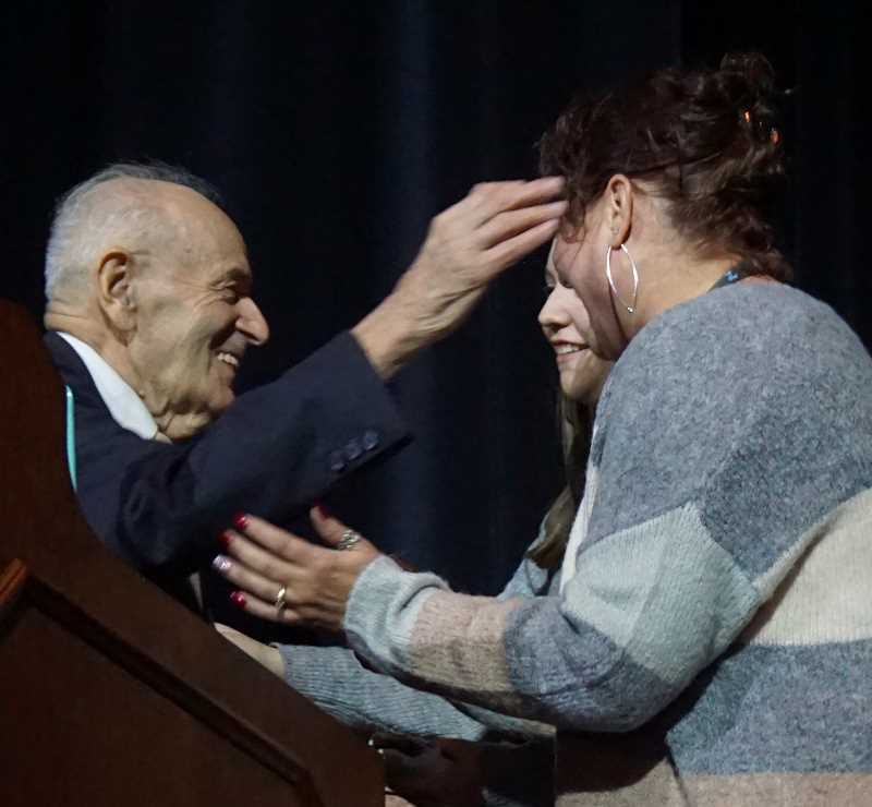 REVIEW PHOTO: CLAIRE HOLLEY - Lakeridge High Principal Desiree Fisher and Pacer freshman Claire Sarnowski embrace Holocaust survivor Alter Wiener after his speech to the school on Dec. 5.