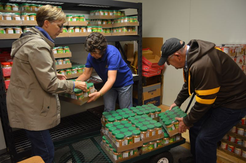 SPOTLIGHT PHOTO: NICOLE THILL-PACHECO - Volunteers Jean Kirsch, Kathy Syrstad and Raymond Justice help stock a storage shelf with jars of donated peanut butter. The St. Helens Backpack Program recently received a donation of 2,200 pounds of peanut butter donated from employees at NuStar Energy.