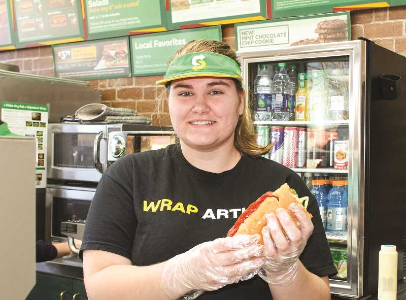 HOLLY SCHOLZ/CENTRAL OREGONIAN  - Prineville Subway Sandwich Artist Mykaela Williams promotes the new Ultimate Spicy Italian Sandwich, which features pepperoni, Genoa salami, garlic butter spread, melted mozzarella and parmesan, plus sauce and veggies.