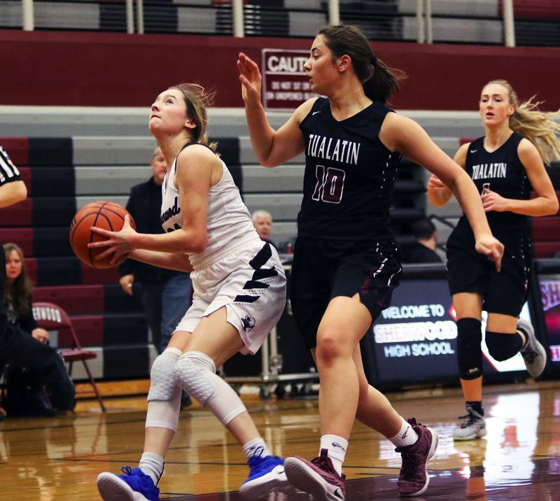 TIMES PHOTO: DAN BROOD - Sherwood junior Ava Boughey (left) looks to go up to the basket against Tualatin sophomore Kasidy Javernick during Tuesday's game.