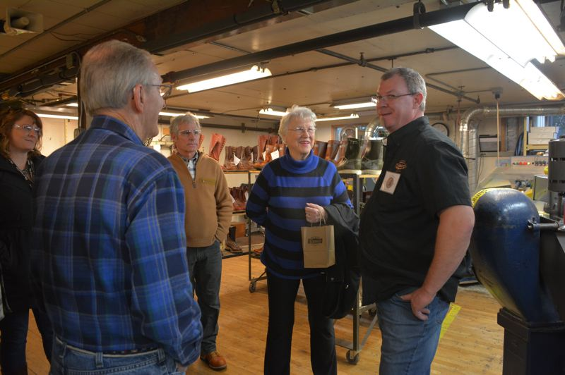 SPOTLIGHT PHOTO: COURTNEY VAUGHN - Kris Oman (right) gives visitors a tour through the Wesco Boots factory in Scappoose during an open house at the boot maker offices Wednesday, Dec. 5. Wesco hosted two open houses for the public and customers to celebrate the companys 100th anniversay.