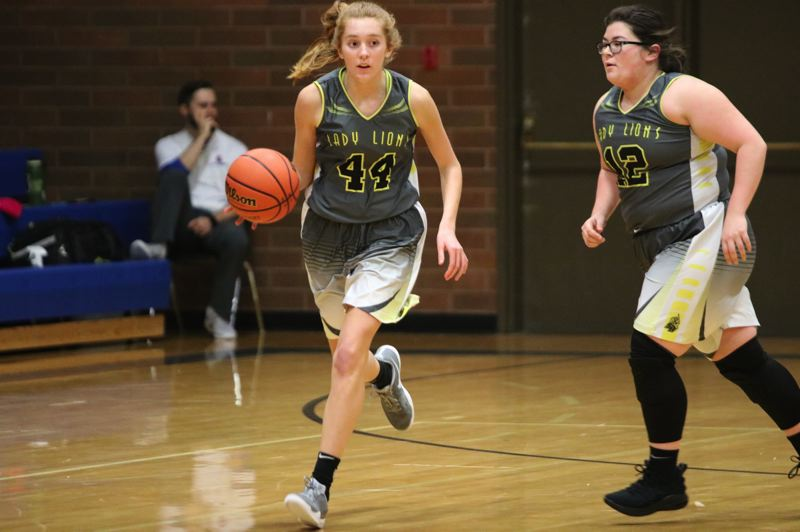 PAMPLIN MEDIA GROUP PHOTO: JIM BESEDA - Maddie Holm (left) brings the ball up the court for St. Helens, as Lions teammate Madisyn Flores moves into position for an offensive play.