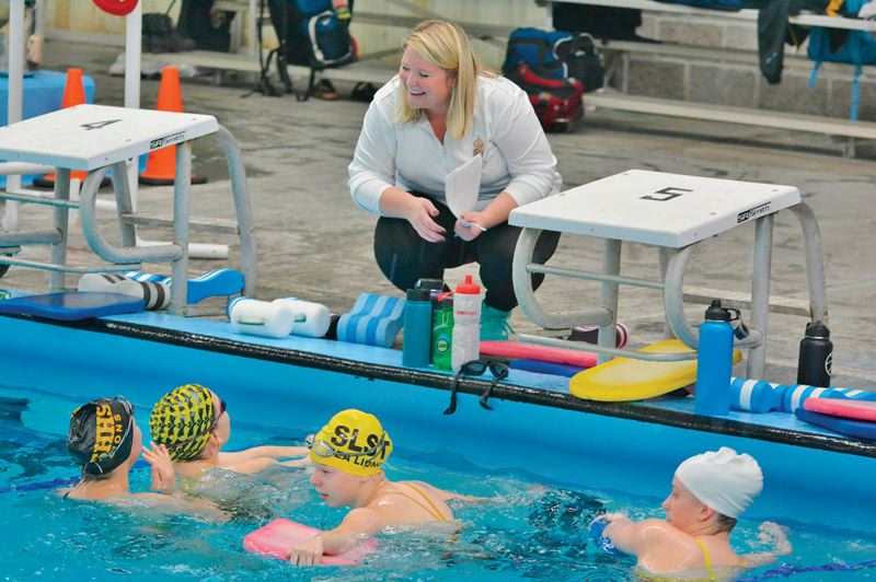 SPOTLIGHT FILE PHOTO - Four St. Helens swimmers confer with coach Christie Orr at a meet last season. From left: now-senior Olea Opdahl, senior Audra Lein, junior Maggie Wheeldon and senior Madeline Watt.